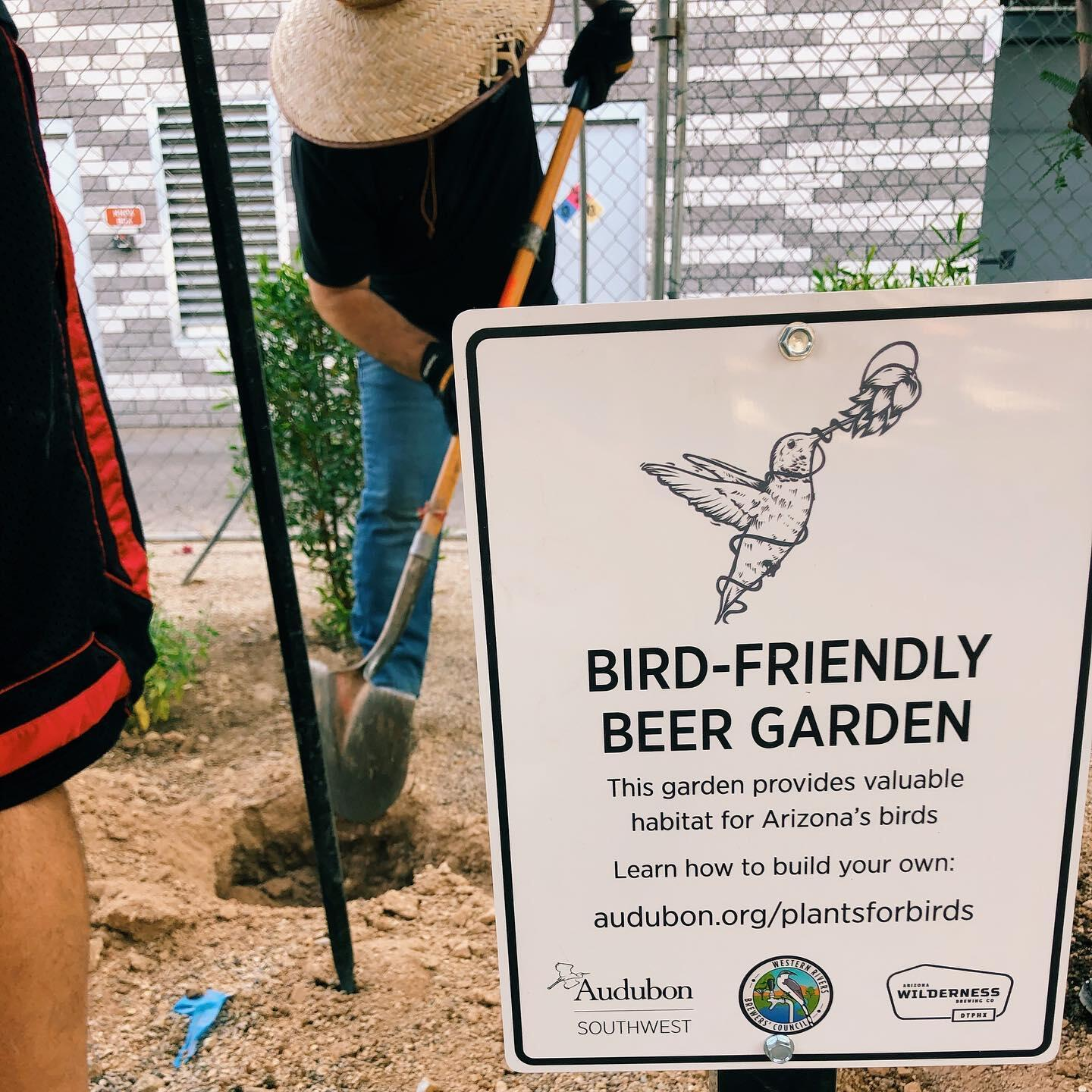 Bird Friendly Beer Garden sign with volunteers planting native plants in the background.