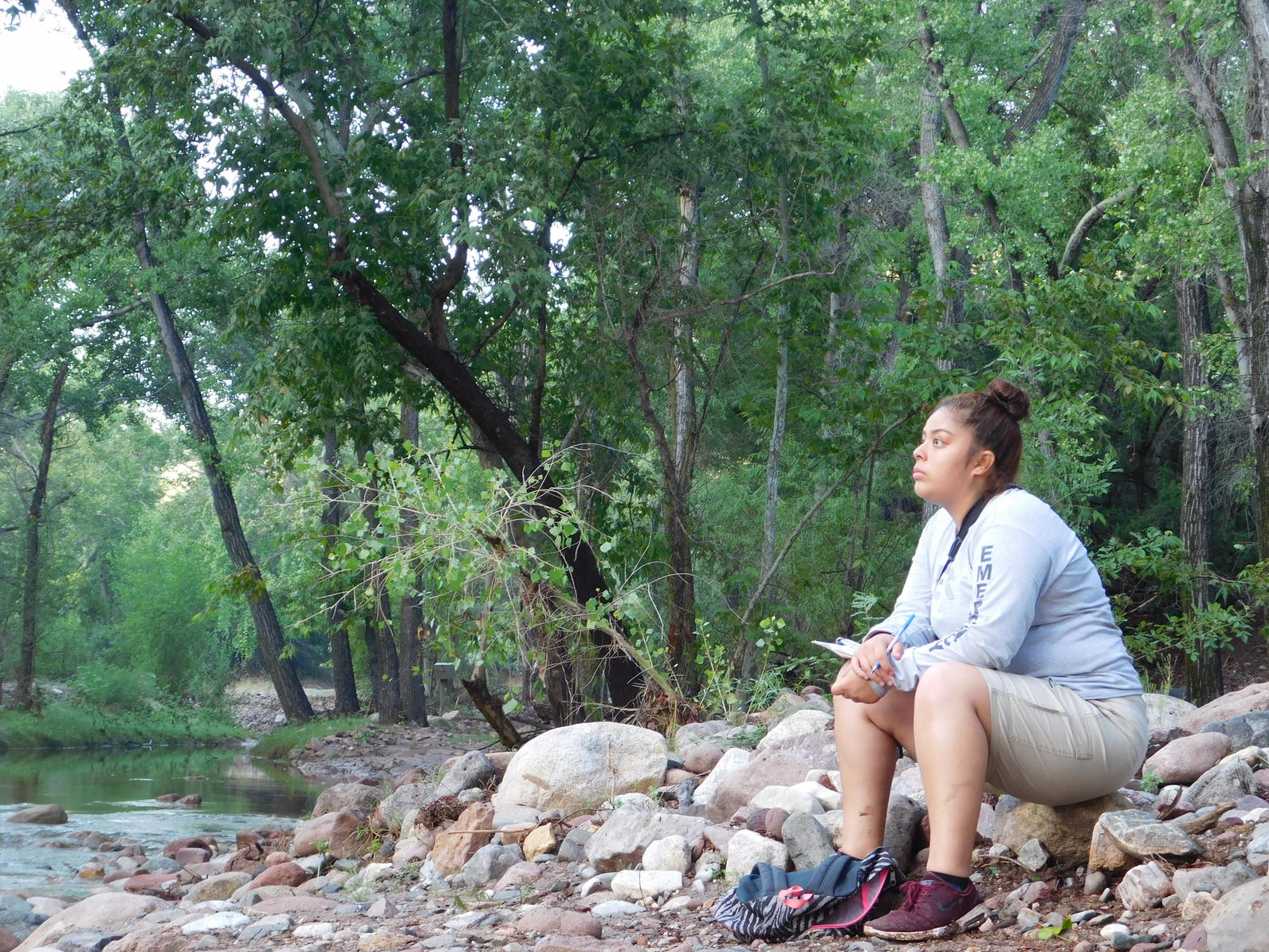 Aritzel Baez, one of last year's summer interns, looks at foliage along the riverbank.