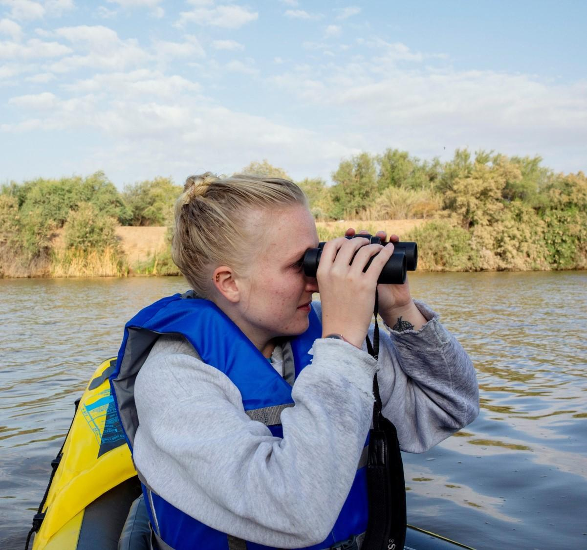 Emma Laurens scopes out a bird with her binoculars in a kayak while surveying for marsh birds on the Gillespie Dam.