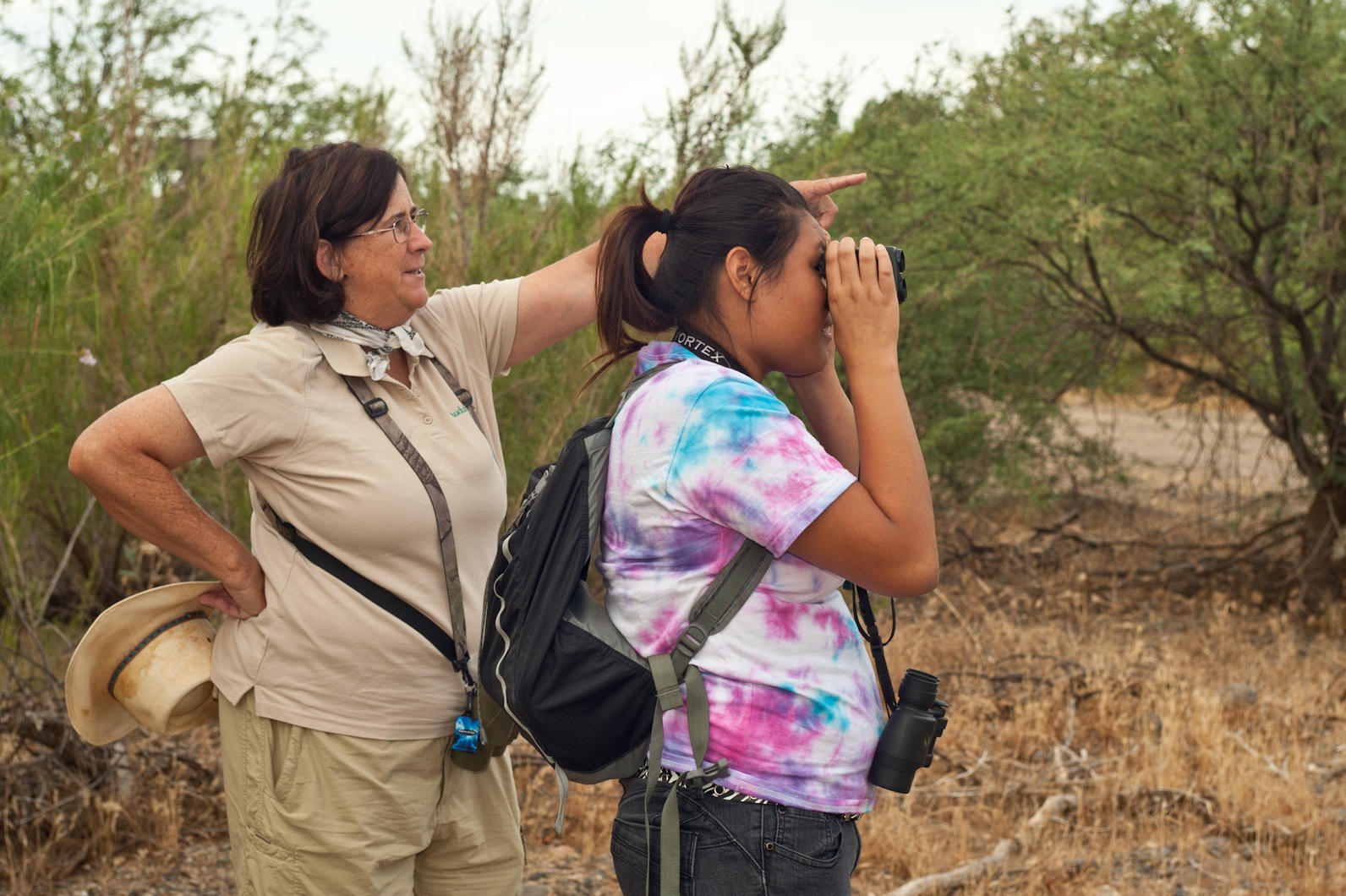 Tice points out a bird to a River Pathways intern.