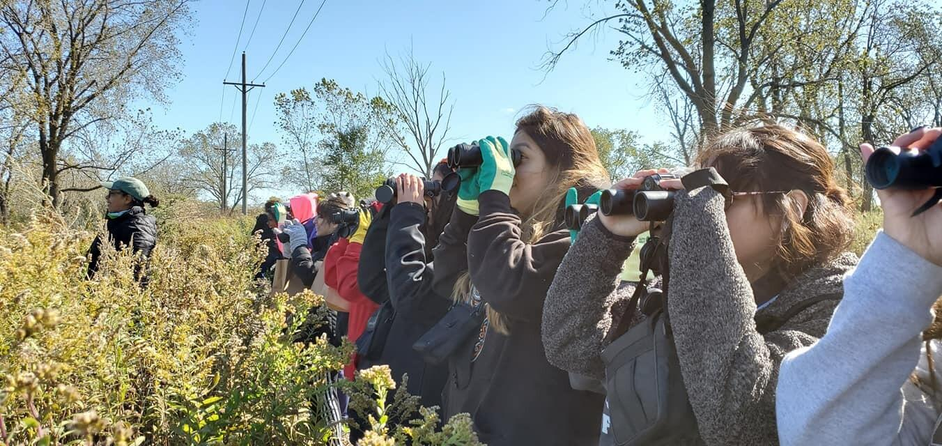 With Carina Ruiz in the lead, a group of young birders look intently through binoculars under clear blue skies.