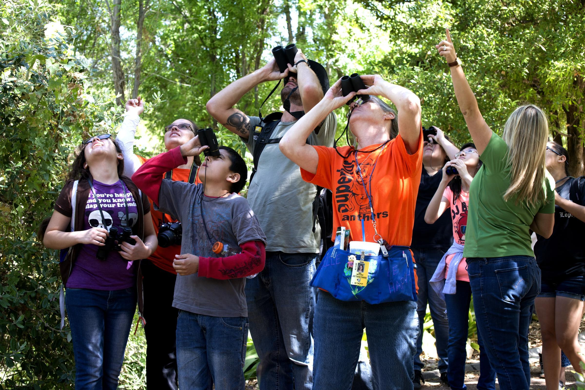 A group of people with binoculars look up into the air.
