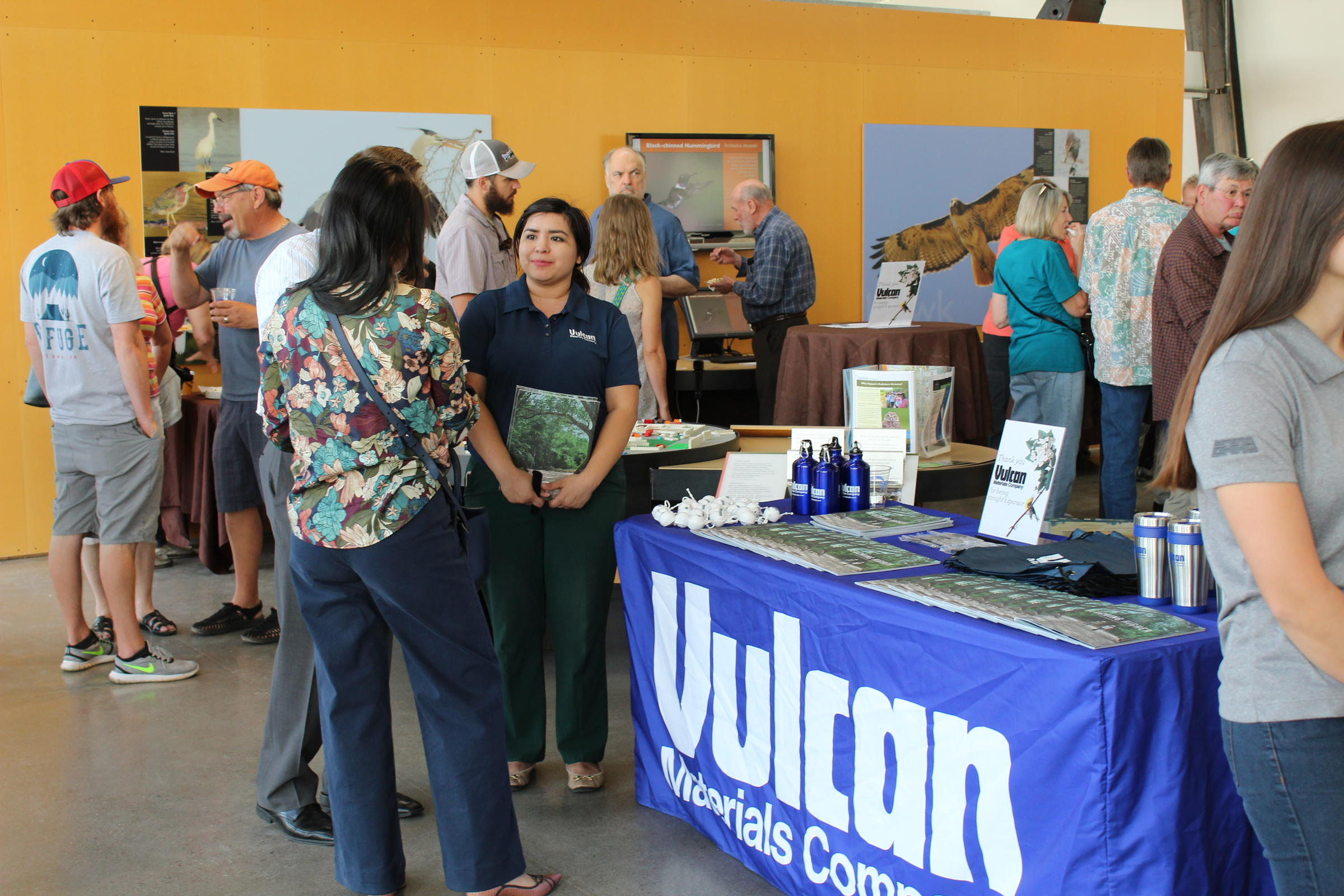 People mingle around the center and interact with a sponsorship booth from Vulcan Materials company during Birds n' Beer.