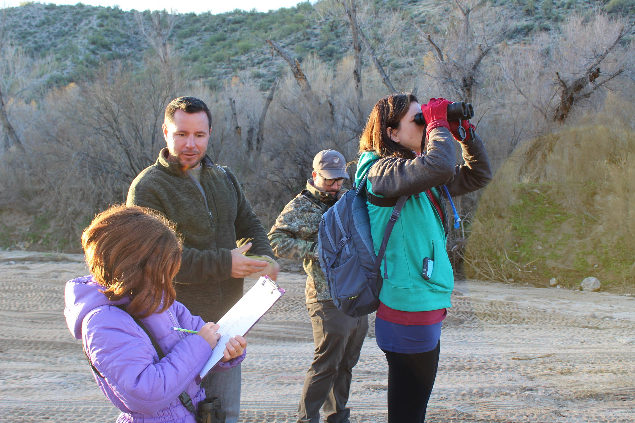 In a dry riverbed, a woman looks at a bird with binoculars while a little girl records the sighting on a piece of paper. Two men in the background get out their binoculars and field guide. It is sunny but also looks cold.