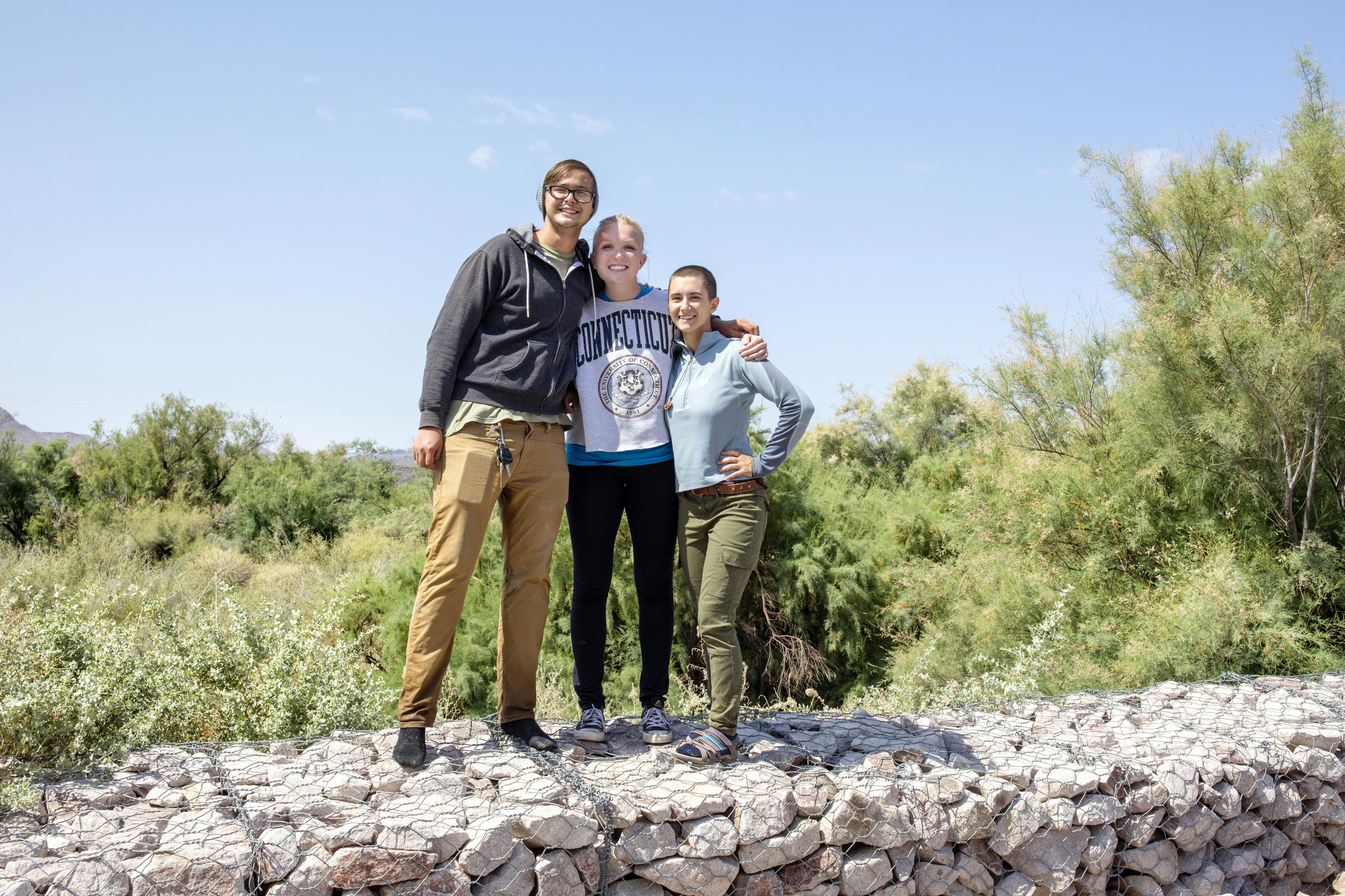 Daniel Hite, Emma Laurens, and Mia McGehee pose together smiling after their marsh bird survey.